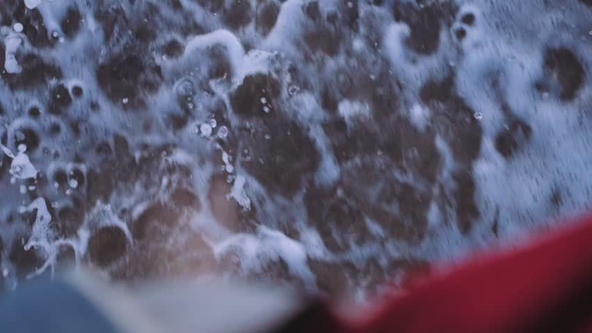 POV slow motion shot of surfer in wet suit or just tourist walk barefeet in shallow water with waves crushing and splashes of salty ocean or sea water up in air.