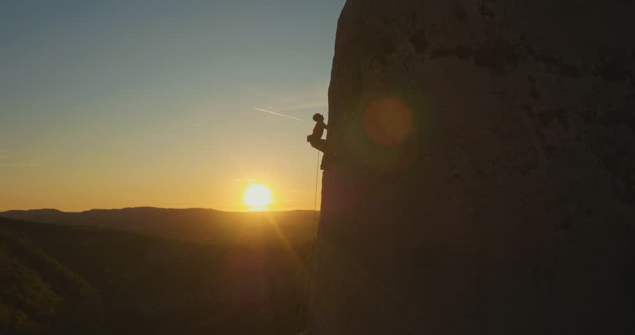 Aerial fly-by a man rock climbing outdoors at amazing sunset. | Shutterstock HD Video #34926604