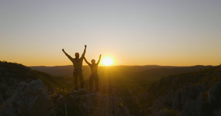 Aerial flight forward - Friends reaching the top and celebrating together at sunset. | Shutterstock HD Video #34926841