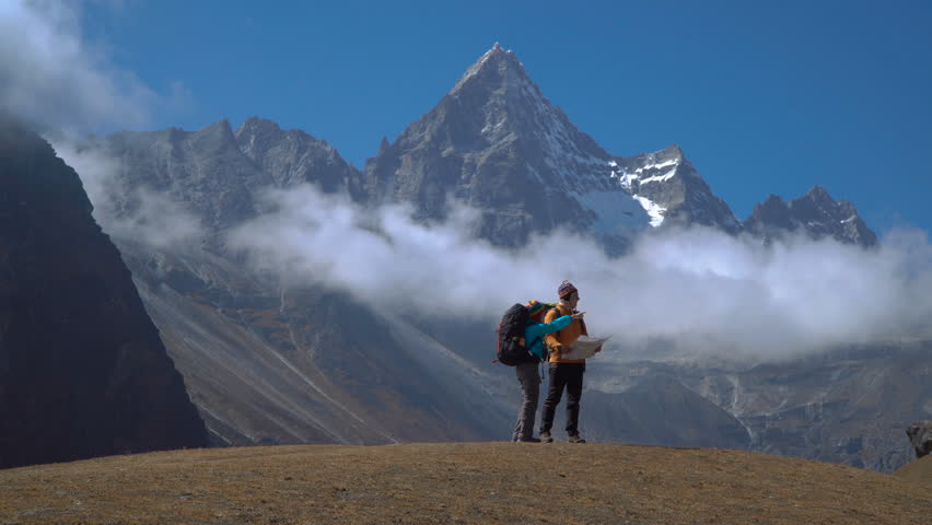 Hikers with backpacks travel in the Himalayan mountains. The map helps you to choose the right path. 4K
