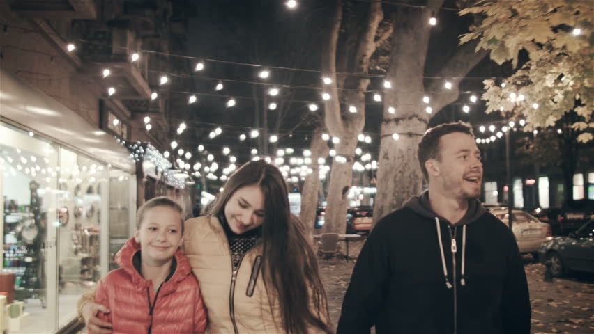 A happy family walks the evening in the city on holidays #34932406