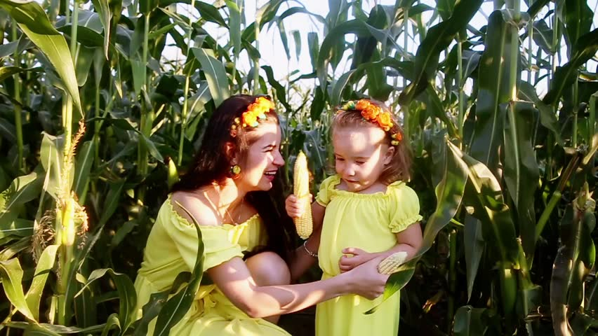 Mom and daughter have fun and sing. Use corn instead of microphone | Shutterstock HD Video #34933939