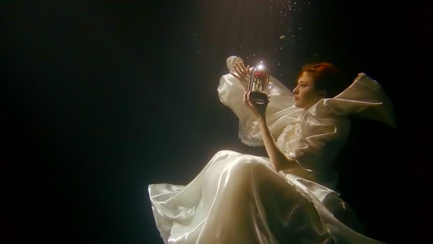 girl is dressed like enchanted princess in luxurious white dress is floating underwater in sun ray