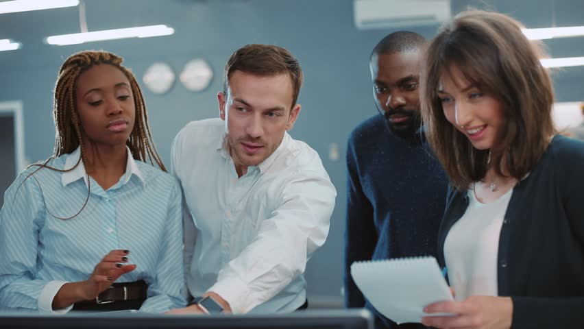 Four attractive young people of different nationalities standing and looking at computer screen in beautiful modern office. Then, colleagues looking at camera and smiling. | Shutterstock HD Video #34937716