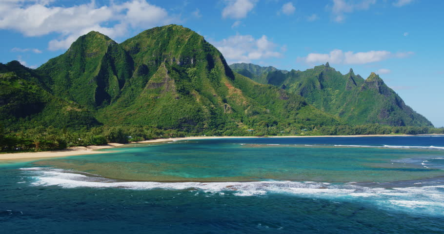 Cinematic aerial view of dramatic mountains and beautiful ocean on North Shore of Kauai