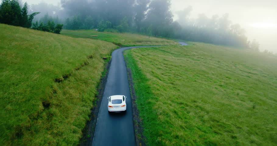 Cinematic aerial view of electric car driving on country road at sunset