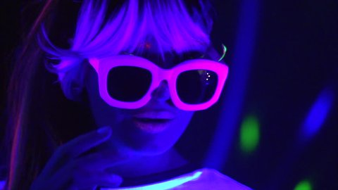 Fashion model woman in neon light, beautiful model girl with fluorescent make-up, Art design of female disco dancer dancing in UV, colorful make up. Night club, Party. 4K UHD slow motion video footage