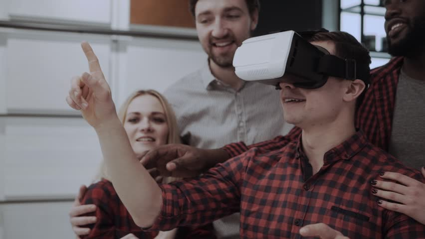 Friends tries app for VR helmet virtual reality glasses his friends and colleagues supporting him in modern office. Multiethnic Business team