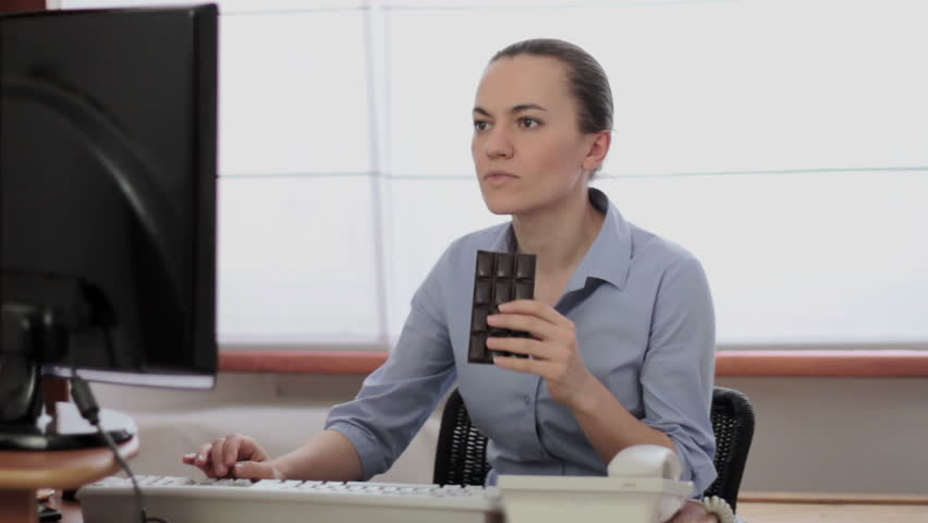 Young business woman eating chocolate at workplace