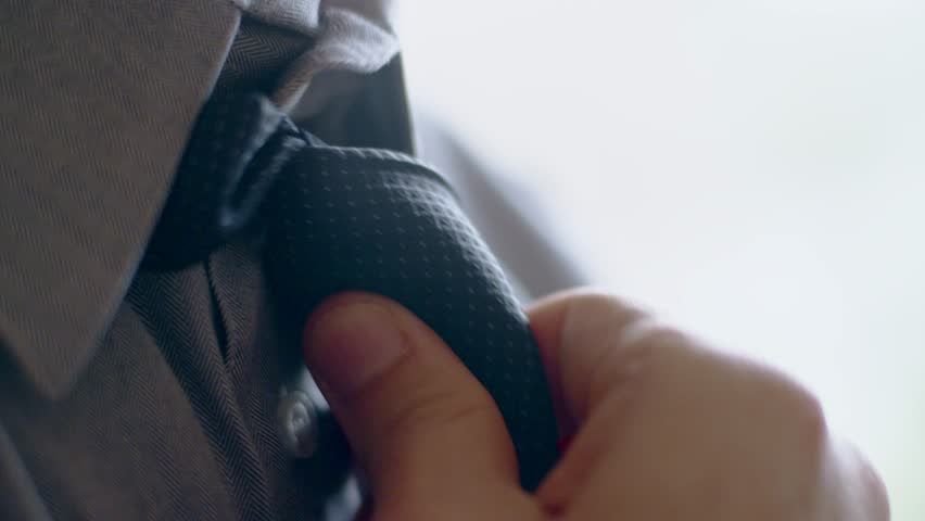 Close-up of hispanic man getting ready tying a necktie in the morning