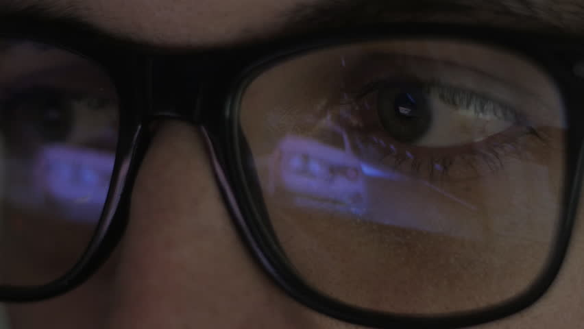 Close-up reflection in glasses: Gamer plays a video game on a computer in a dark room | Shutterstock HD Video #34982467