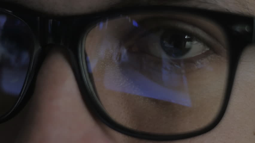 Close-up reflection in glasses: Gamer plays a video game on a computer in a dark room | Shutterstock HD Video #34982476