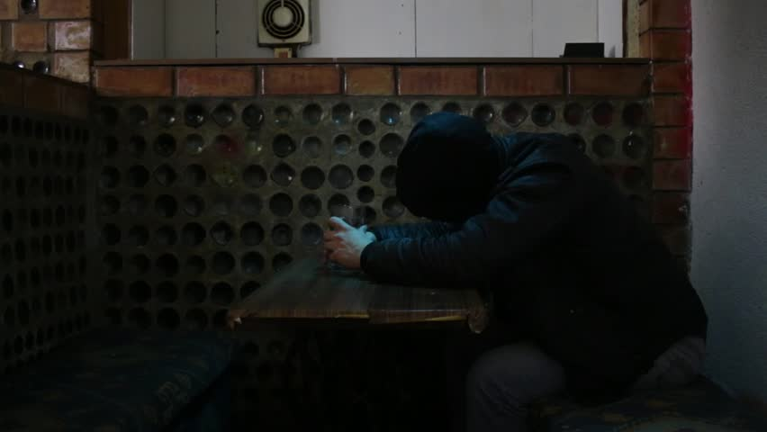 A man in a hood sleeps at the table in the bar2