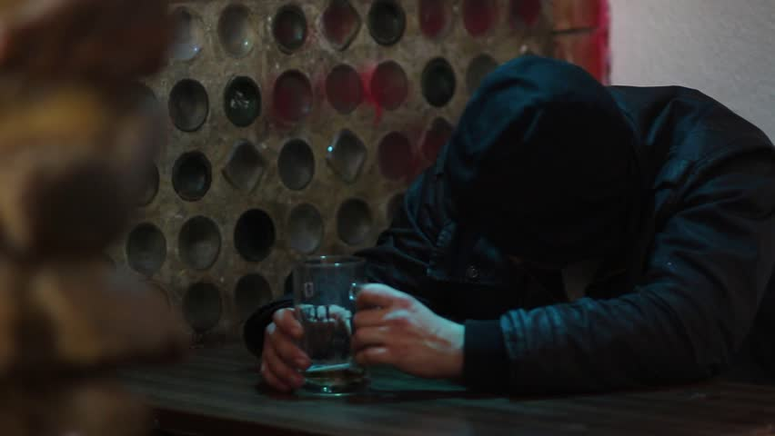 A man in a hood sleeps at the table in the bar