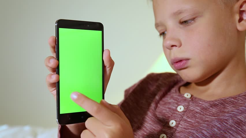 Mockup video of cute funny smiling kid laying in bed in home interior. Closeup profile portrait of child holds modern mobile phone with blank green screen in hands. Real time full hd video footage. | Shutterstock HD Video #35009524