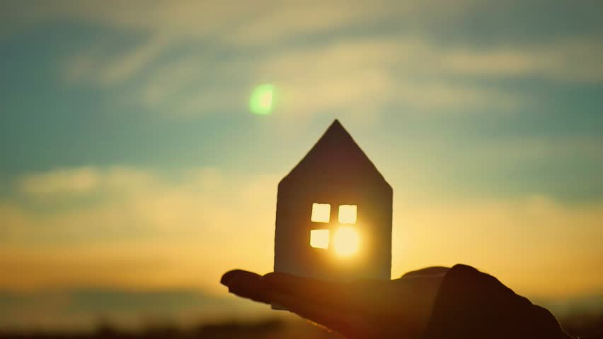Silhouette hand with paper house at sunset background.
