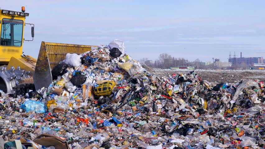 A high pile of trash moved by a landfill truck. Water, air contamination concept.
