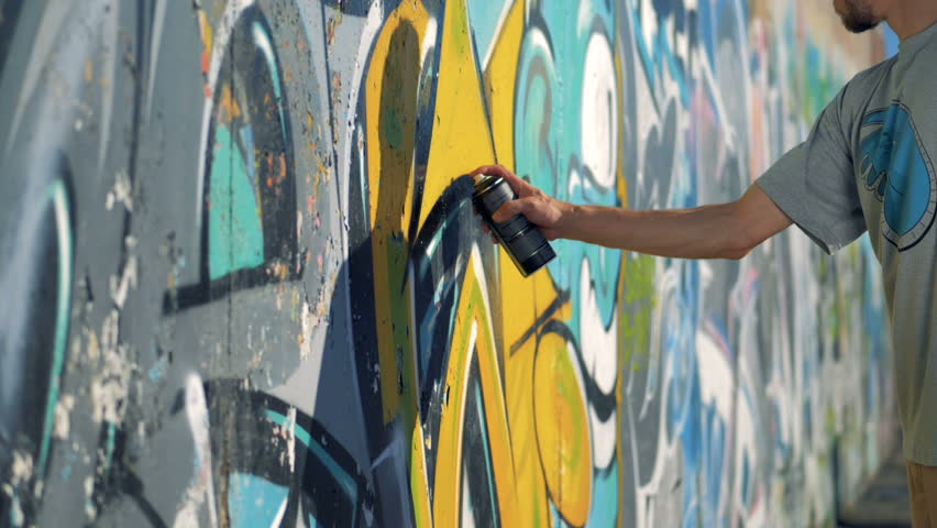 A graffitist contours the paintings edges with black color.