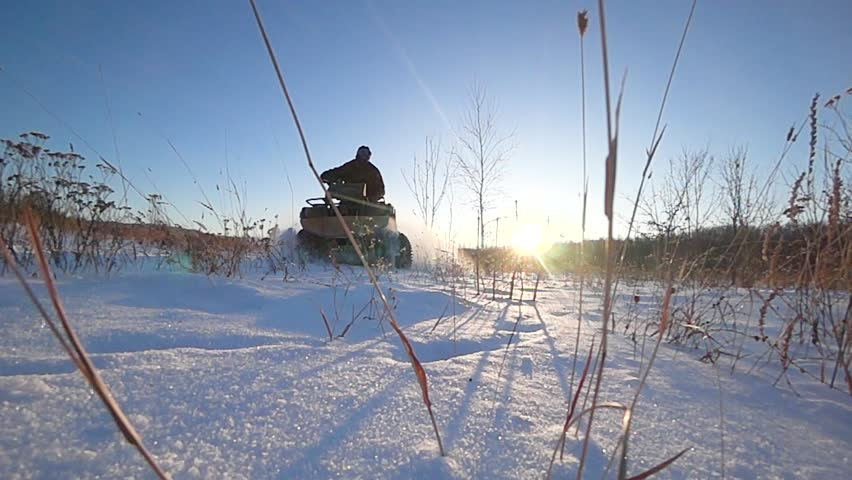 ATV riding in the snow backlight speed slow shooting