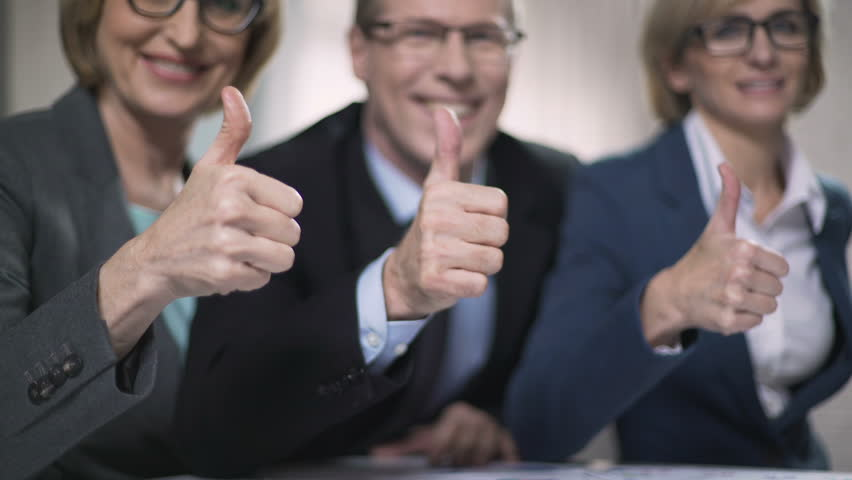 Happy business people with thumbs up, satisfied with successful presentation