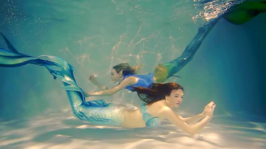 Couple of happy mermaids swims.