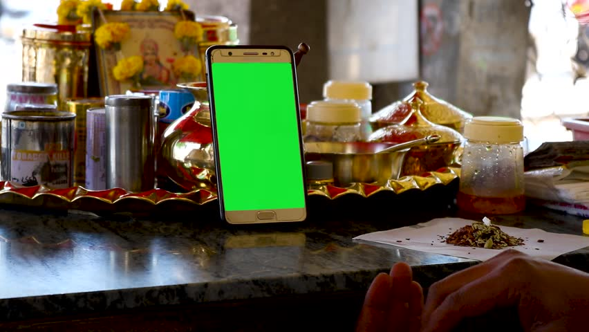 Indian shopkeeper working and surfing internet on mobile ( green screen display ) useful for mobile advertisment application - digital marketing