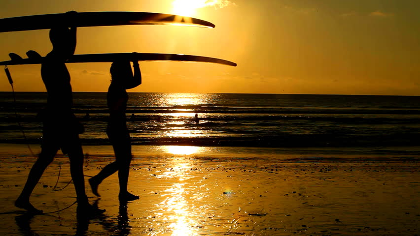 Surfer couple in silhouette walking with long surf boards at sunset on tropical beach | Shutterstock Video #3509429