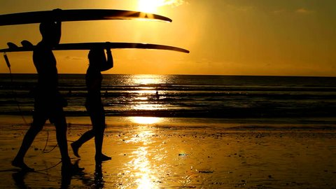 Surfer couple in silhouette walking with long surf boards at sunset on tropical beach