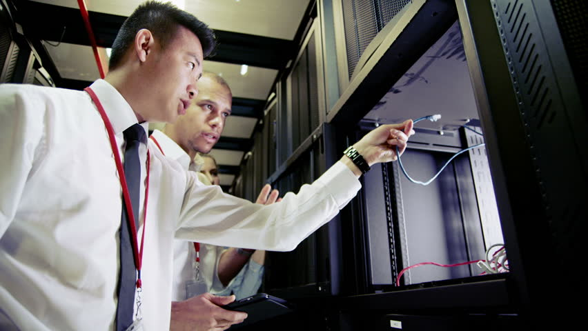 Three people of mixed ethnicity are working in a data center with rows of server racks and super computers. They are walking up and down and checking all of the equipment.  | Shutterstock HD Video #3510914