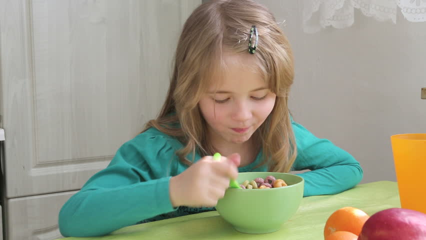 young girl eating cornflakes from the bowl