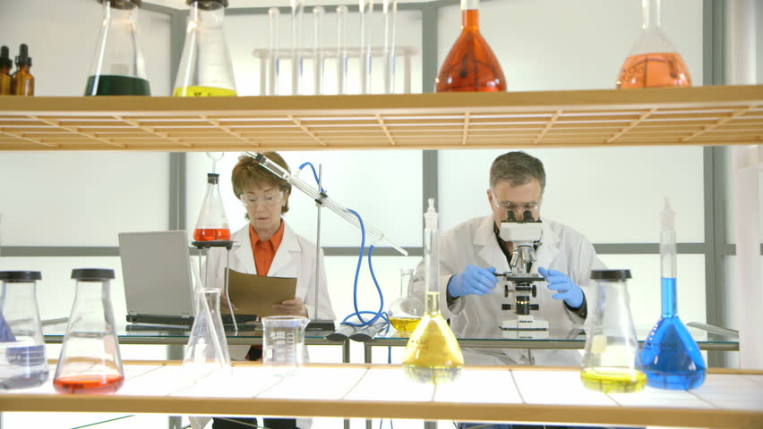Laboratory flasks and other glassware in the foreground of footage of two scientists working in their lab. #3536204