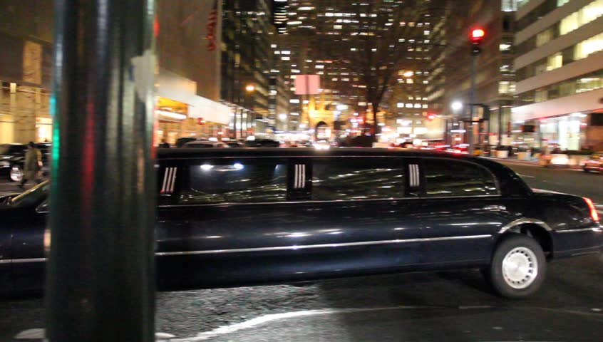 New York, NY - Circa 2012: Multiple Limousines in NYC at night drive the streets looking for customers waiting on the sidewalks