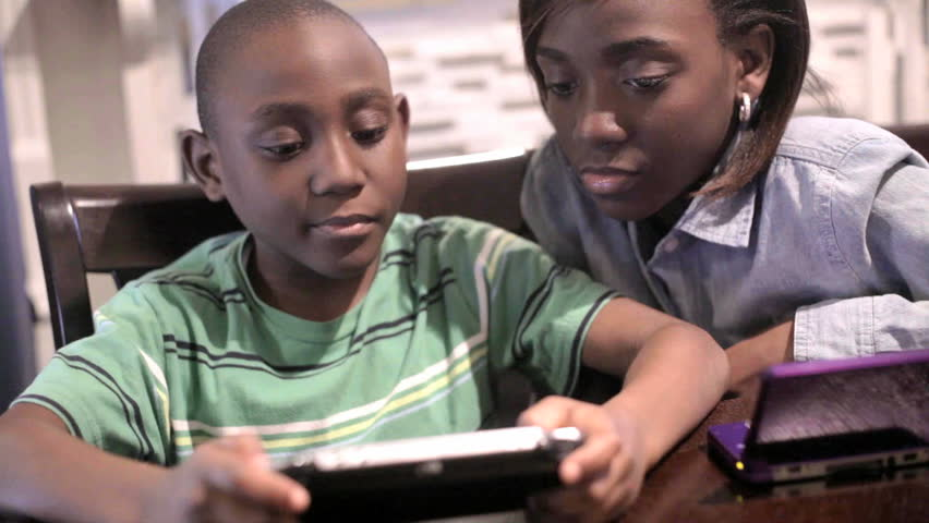 African American Black Boy and girl playing video games in the kitchen