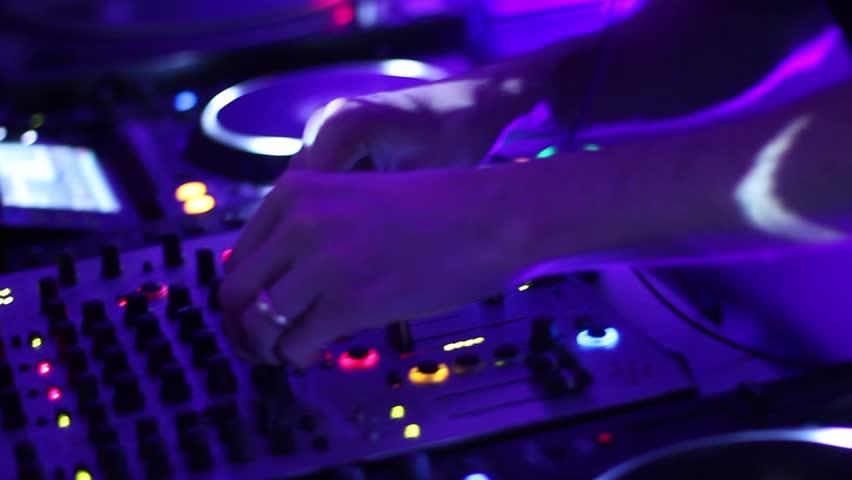 Hands of DJ tweak various track controls on dj's deck, camera is breathing
