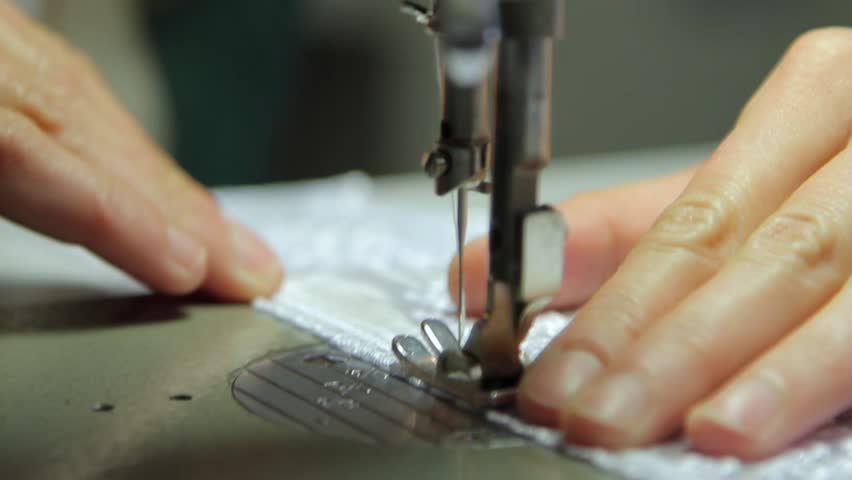 A hand of a dressmaker supporting a cloth while sewing on a sewing machine.