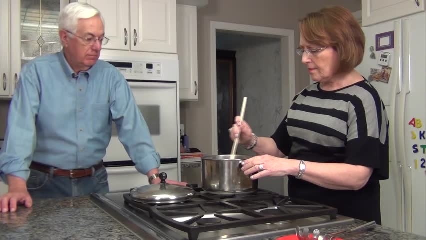 Senior Couple cooking chili together in remodeled white kitchen
