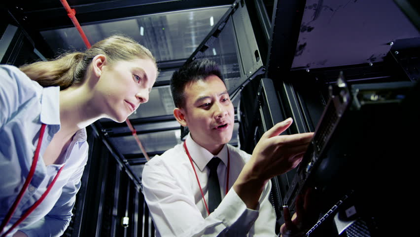 Two IT engineers are working in a data center with rows of server racks and super computers. They are discussing their work as they check cables and other equipment. In slow motion.   Shutterstock HD Video #3589157