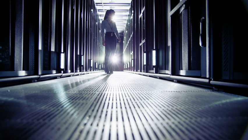 Attractive female IT engineer is working in a data centre with rows of server racks and super computers. She is walking up and down and checking all of the equipment.  | Shutterstock HD Video #3589322