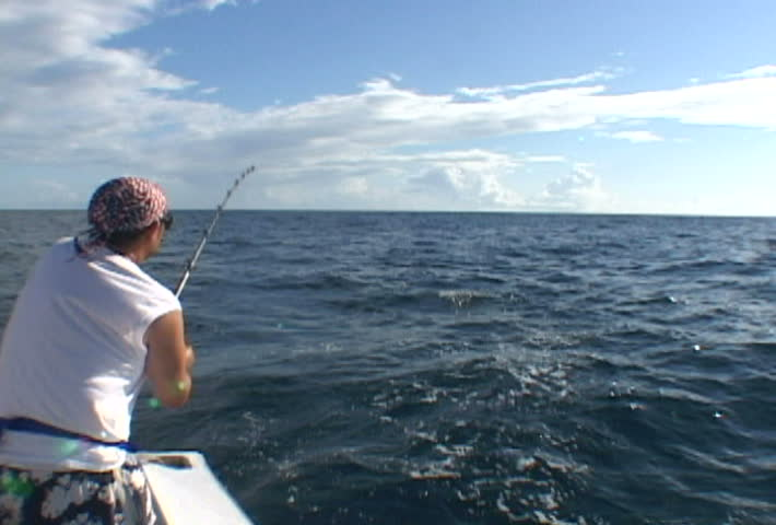 Man in Florida catching King fish from boat.