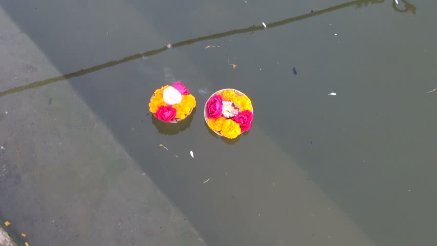 hinduism religious ritual puja flowers and candle on Ganges water, India