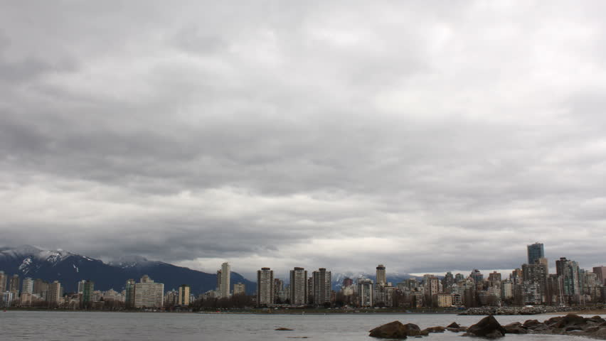 Vancouver Skyline Time Lapse. A time lapse view across English Bay, the apartments and condominiums of the West End, and the snow capped North Shore Mountains in Vancouver, British Columbia, Canada.