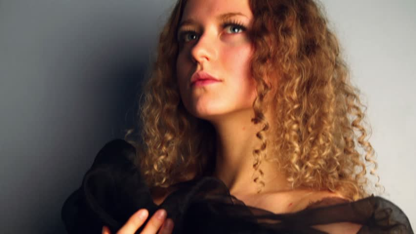 Young model with curly hair stands near wall wrapped in black shawl, shown in motion