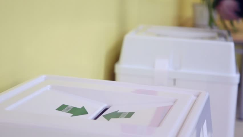 Hands of people drop ballots in box with Bulletin inscription during voting, closeup