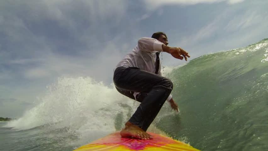 Cheerful businessman on surf board rides a tropical ocean wave