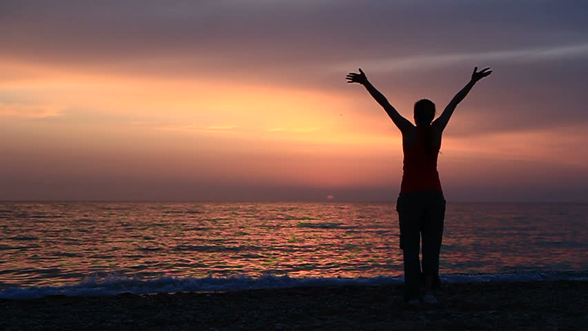 Young woman is waving hands standing on the beach. Slow motion,two frames.