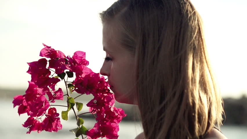 Young woman standing on seashore and smelling flower, slow motion shot at 240fps  #3646799