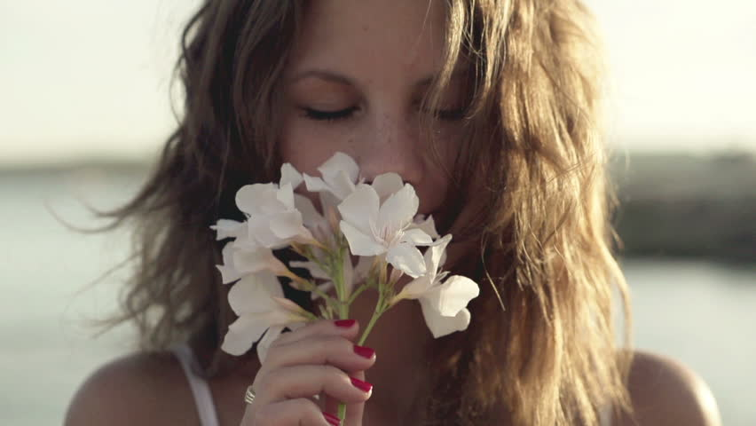 Young woman standing on seashore and smelling flower, slow motion shot at 120fps  #3647189