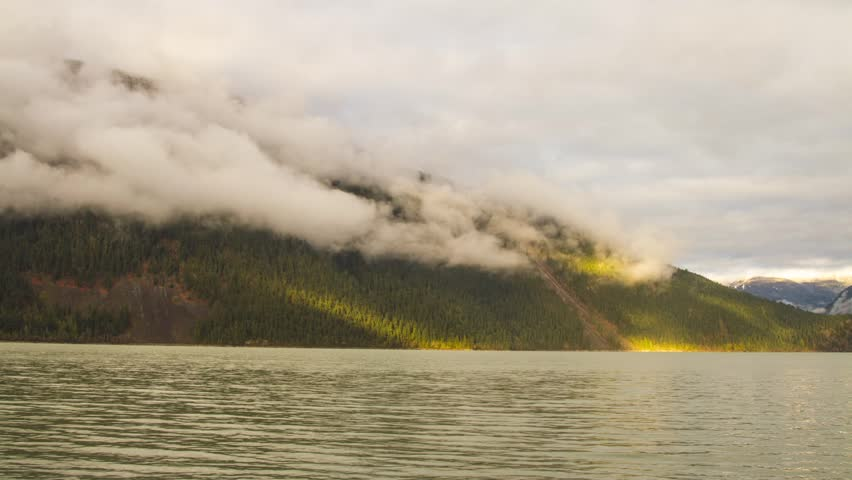 Foggy Morning with Sun Light Shining on a Mountain at Lillooet Lake in BC, Canada. Photo Sequence shot in RAW and Post-Production in After Effects.