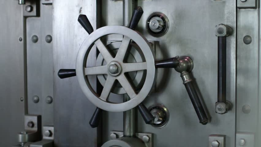 Woman opens a large bank vault door. Close up.