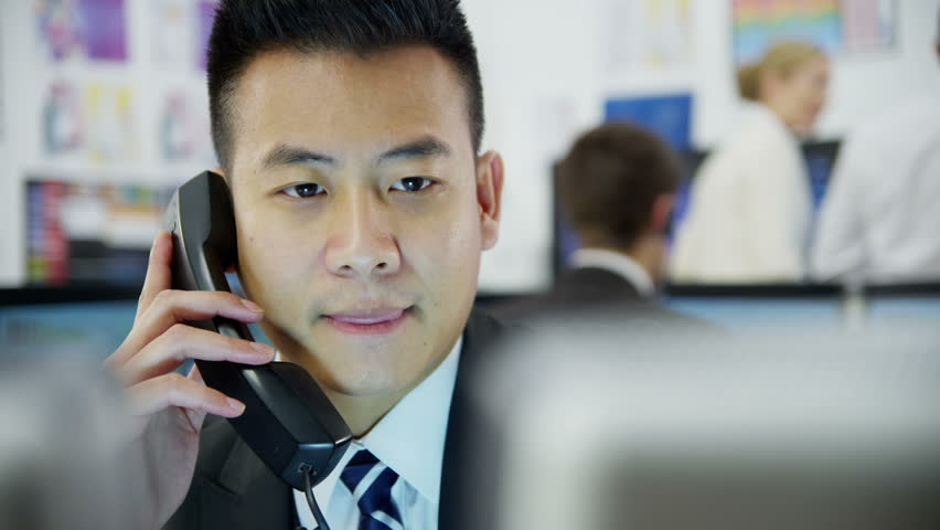 Young and ambitious stock market trader is doing a deal over the phone in a busy office filled with computers. The rest of his team are hard at work in the background.  | Shutterstock HD Video #3673151